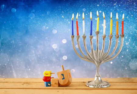 hanukiah: image of jewish holiday Hanukkah with menorah traditional Candelabra and wooden dreidels spinning top. retro filtered image Stock Photo