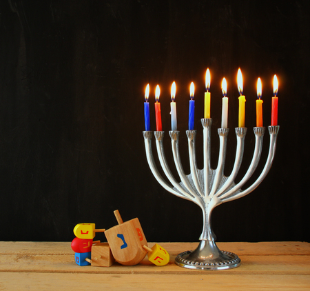 image of jewish holiday Hanukkah with menorah traditional Candelabra and wooden dreidels spinning top. retro filtered image Stock Photo
