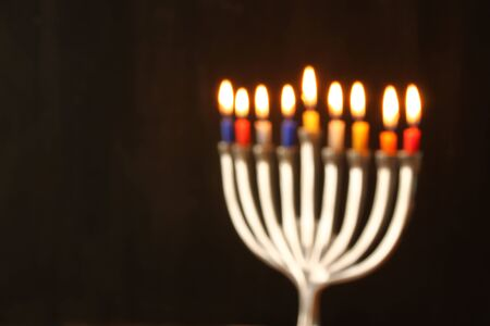 hanukiah: abstract blurred background of jewish holiday Hanukkah background with menorah traditional candelabra Burning candles over black background
