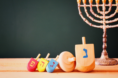 judaica: low key image of jewish holiday Hanukkah with menorah traditional Candelabra and wooden dreidels spinning top over chalkboard background, room for text Stock Photo