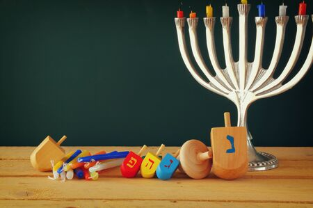 menora: low key image of jewish holiday Hanukkah with menorah traditional Candelabra and wooden dreidels spinning top over chalkboard background, room for text Stock Photo