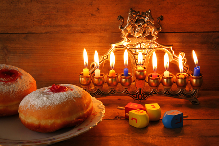 dreidel: image of jewish holiday Hanukkah with menorah traditional Candelabra, donuts and wooden dreidels spinning top