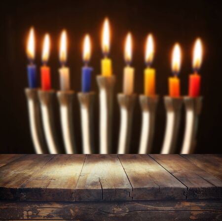 hanukkah: Image of jewish holiday Hanukkah background with menorah traditional candelabra Burning candles and wooden table Stock Photo