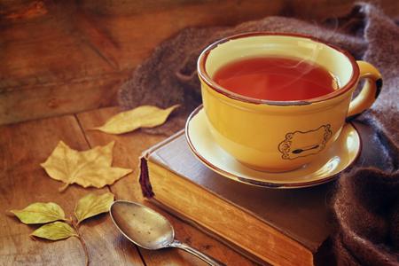 taza de té: Taza de té con el libro viejo, hojas de otoño y una bufanda caliente en la mesa de madera