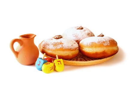 jewish background: image of jewish holiday Hanukkah with donuts, traditional chocolate coins and wooden dreidels spinning top. isolated on white Stock Photo