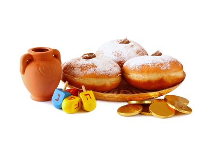 dreidels: image of jewish holiday Hanukkah with donuts, traditional chocolate coins and wooden dreidels spinning top. isolated on white Stock Photo