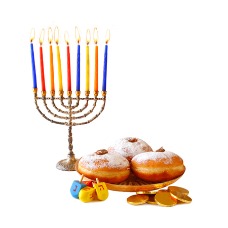 jewish background: image of jewish holiday Hanukkah with menorah traditional Candelabra, donuts and wooden dreidels spinning top.isolated on white Stock Photo