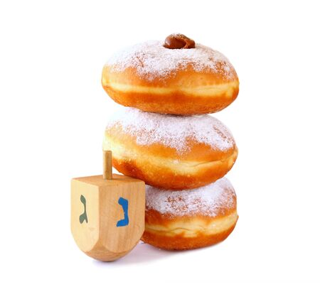 dreidel: image of jewish holiday Hanukkah with donuts and wooden dreidel spinning top. isolated on white Stock Photo