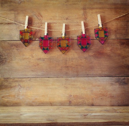 dreidels: image of jewish holiday Hanukkah with Stained-glass colorful dreidels spinning top hanging on a rope over wooden background