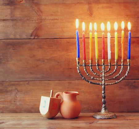 chanukiah: low key image of jewish holiday Hanukkah with menorah traditional Candelabra and wooden dreidels spinning top