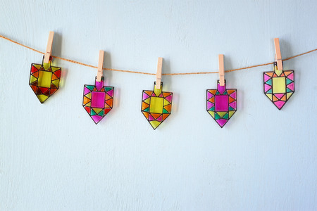 chanukah: image of jewish holiday Hanukkah with Stained-glass colorful dreidels spinning top hanging on a rope over wooden background