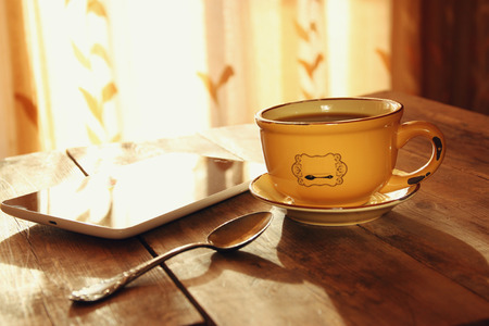 old windows: Cup of tea with tablet device next to window on wooden table Stock Photo