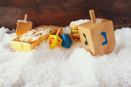 dreidels: image of jewish holiday Hanukkah with wooden colorful dreidels spinning top over december snow. copy space