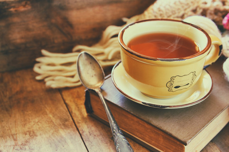 Cup of tea with old book, autumn leaves and a warm scarf on wooden table Stock Photo