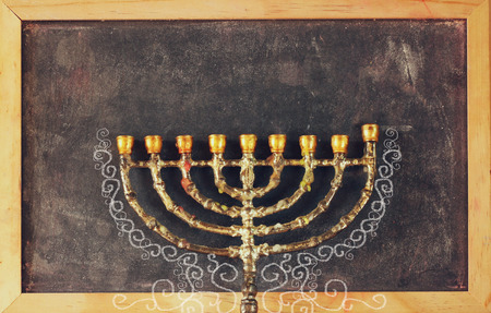 hanukiah: image of jewish holiday Hanukkah with menorah traditional Candelabra over chalkboard background, room for text Stock Photo