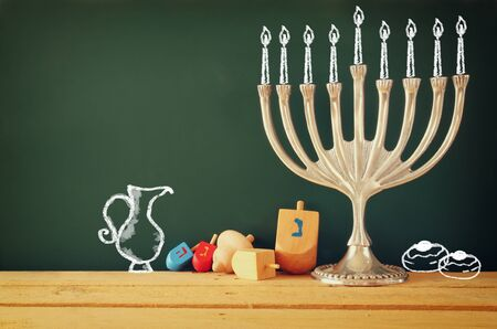 judaica: image of jewish holiday Hanukkah with drawing menorah candles traditional Candelabra, donuts and wooden dreidels spinning top over chalkboard background