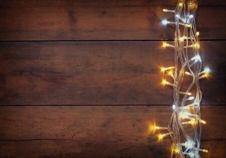 christmas gold: Christmas warm gold garland lights on wooden rustic background. filtered image Stock Photo