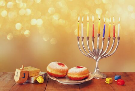 Image of jewish holiday Hanukkah background with menorah traditional candelabra and Burning candles with glitter overlay