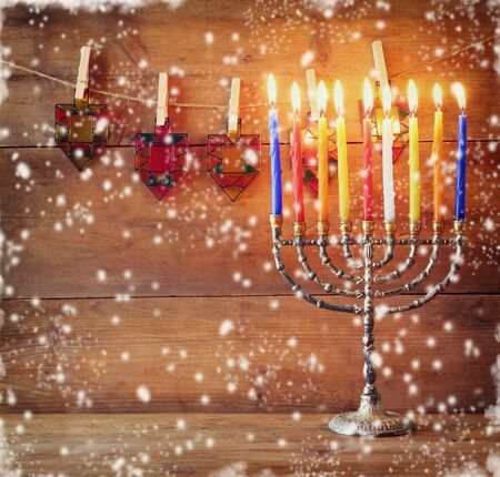 chanukkah: Image of jewish holiday Hanukkah background with menorah traditional candelabra and Burning candles. abstract snow overlay Stock Photo