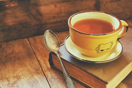 hojas antiguas: Copa del ingenio té hojas viejas libro h otoño y una bufanda caliente en la mesa de madera