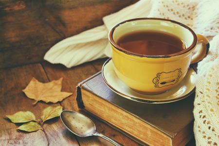 hojas antiguas: Copa del ingenio té hojas viejas libro h otoño y un suéter caliente en la mesa de madera Foto de archivo