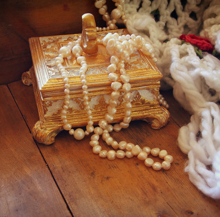 antique jewelry: A beautiful antique golden jewelry box with natural white pearls on wooden table