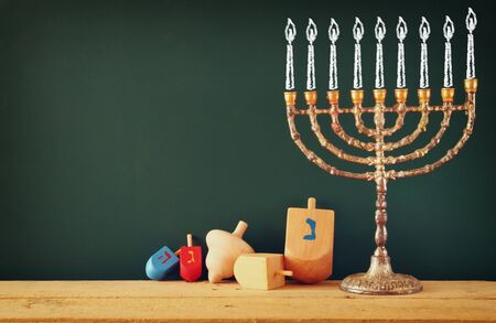 chanukah: image of jewish holiday Hanukkah with drawing menorah candles traditional Candelabra, wooden dreidels spinning top over chalkboard background