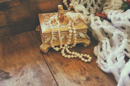 perlas: Una hermosa antigua caja de joyería de oro con perlas blancas naturales en mesa de madera. retro imagen filtrada