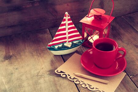 sailboats: red cup of tea and letter paper next to vintage decorative boat and lantern on wooden old table. retro filtered image