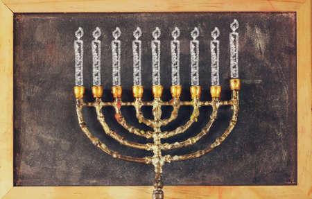 chanukiah: image of jewish holiday Hanukkah with drawing menorah candles traditional Candelabra over chalkboard background