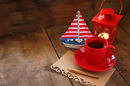 tea table: red cup of tea and letter paper next to vintage decorative boat and lantern on wooden old table. retro filtered image