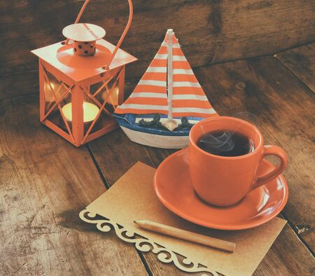 writing desk: red cup of tea and letter paper next to vintage decorative boat and lantern on wooden old table. retro filtered image
