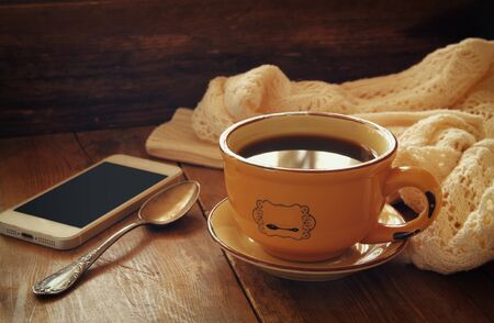life style: Cup of tea with smartphone on wooden table