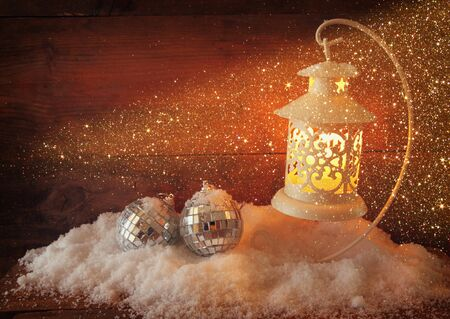 christmas candles: christmas background with white lantern, bauble and snow over wooden background Stock Photo