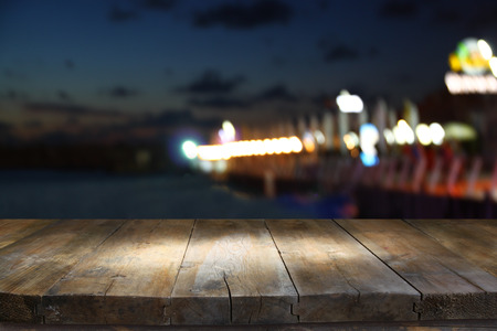 night table: image of wooden table in front of abstract blurred background of restaurant lights