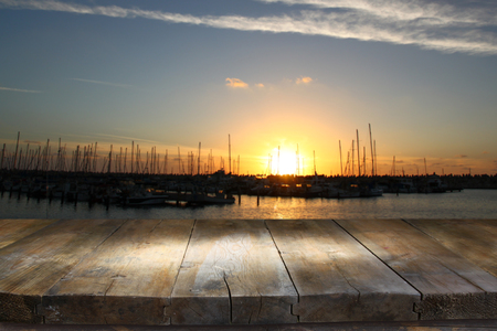 night table: image of wooden table in front of abstract blurred background of marina yacht in pier at sunset Stock Photo