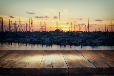 image of wooden table in front of abstract blurred background of marina yacht in pier at sunset Stockfoto