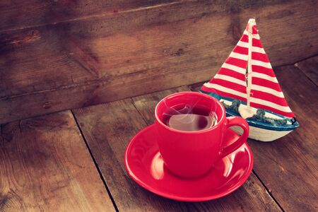 red cup of tear next to vintage decorative boat on wooden old table. retro filtered image Stock Photo