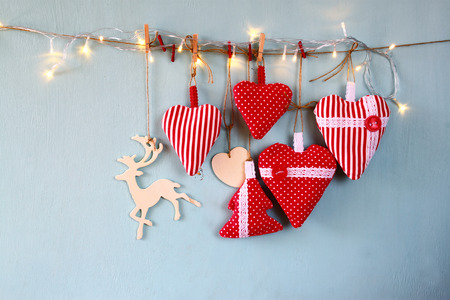 wooden reindeer: christmas image of fabric red hearts and tree. wooden reindeer and garland lights, hanging on rope in front of blue wooden background. retro filtered