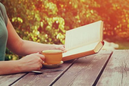 woman happy: close up image of woman reading book outdoors, next to wooden table and coffee cup at afternoon. filtered image. filtered image. selective focus