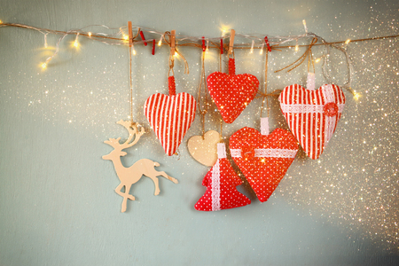 rope: christmas image of fabric red hearts and tree. wooden reindeer and garland lights, hanging on rope in front of blue wooden background. retro filtered