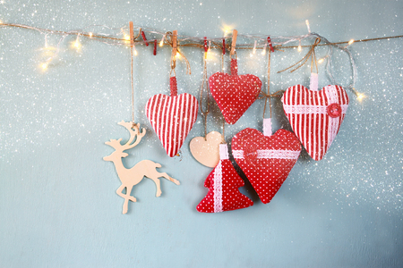 wooden reindeer: christmas image of fabric red hearts and tree. wooden reindeer and garland lights, hanging on rope in front of blue wooden background