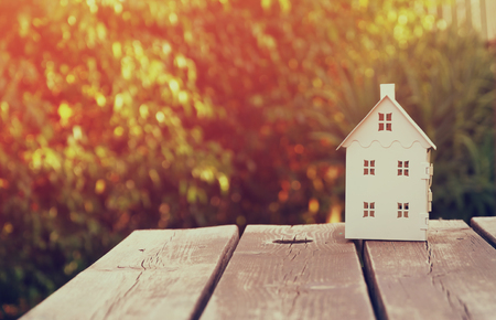 home sale: small house model over wooden table outdoors at garden selective focus . filtered image