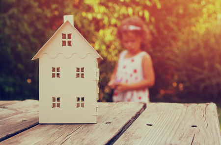 children at play: small house model over wooden table outdoors at garden and kid playing. selective focus . filtered image Stock Photo