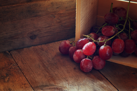 the grapes: low key image of red grapes over wooden textured table Stock Photo