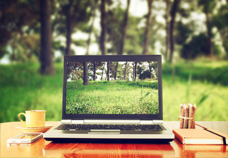 prespective: laptop over wooden table outdoors and blurred background of trees in the forest
