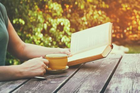 imagen: de cerca la imagen del libro de lectura de la mujer al aire libre, junto a la mesa de madera y una taza de caf� en la tarde. filtrada imagen. filtrada imagen. enfoque selectivo
