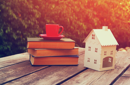 a small house: coffee cup mug and book over wooden table outdoors, at afternoon time. small house model over wooden table outdoors at garden. filtered image, selective focus