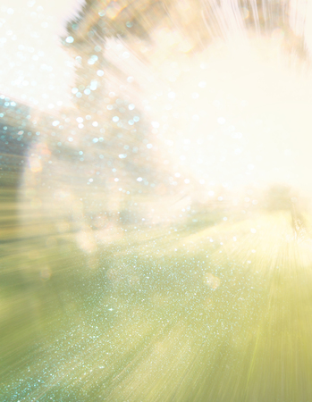 blurred abstract photo of light burst among trees and glitter bokeh lights. filtered image and textured. Stock fotó