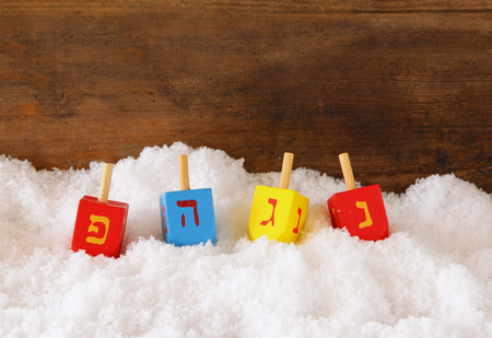 hanoukia: image of jewish holiday Hanukkah with wooden colorful dreidels spinning top and chocolate traditional coins over december snow Banque d'images